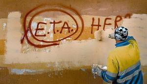 Un técnico de limpieza borra una pintada a favor de ETA en Gernika (Vizcaya), el día después de que la banda terrorista anunciase el cese definitivo de sus acciones armadas.