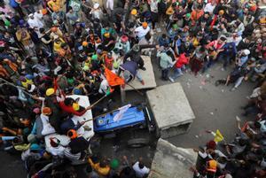 Un grupo de agricultores intenta abriese paso con sus tractores entre las barricadas que protegen el centro de Nueva Delhi.