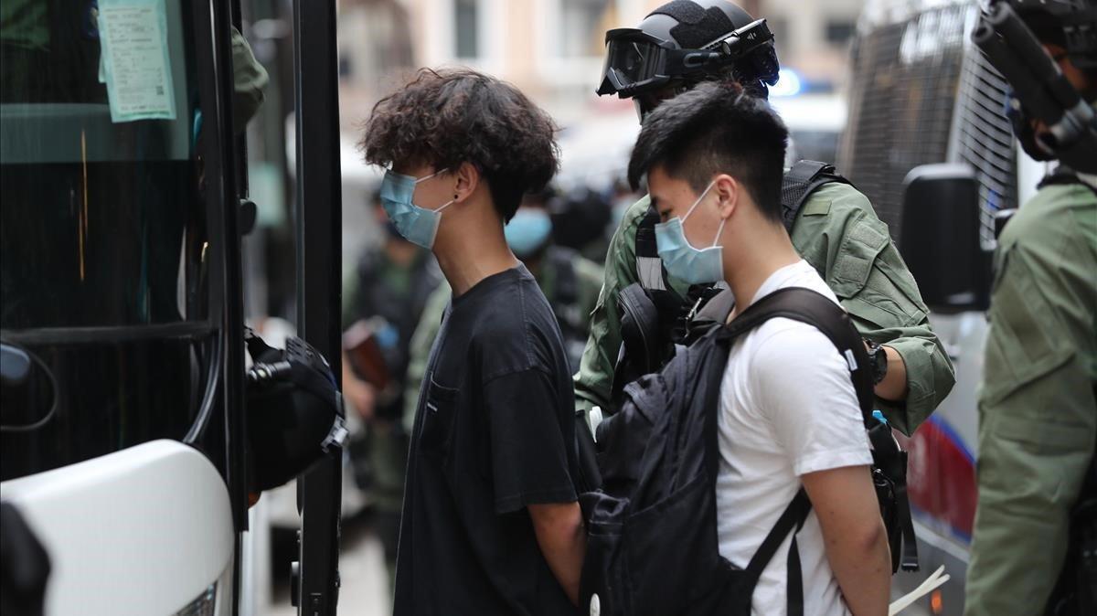 Dos jóvenes arrestados en Hong Kong este jueves.