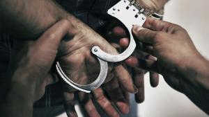 Un hombre detenido por agentes policiales.