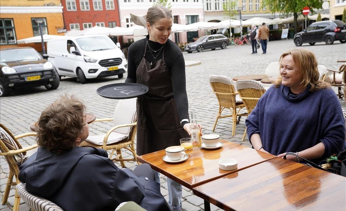 Dos personas degustan un café, en una terraza de Copenhague.