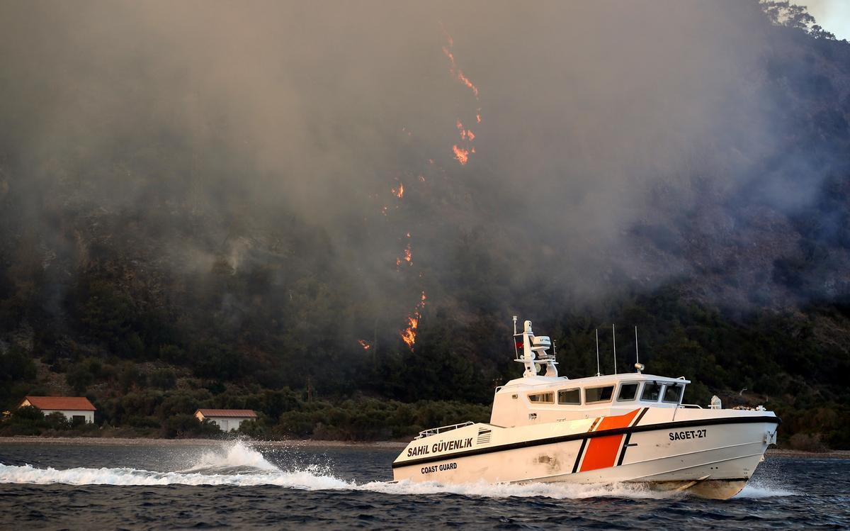 Un barco de la Guardia Costera huye de las llamas en Turquía.