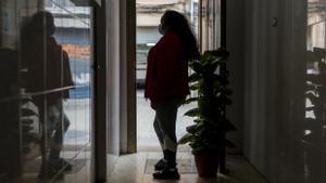 Mariana V., inmigrante ecuatoriana acosada por las deudas, en el portal de su casa en Cornellà.