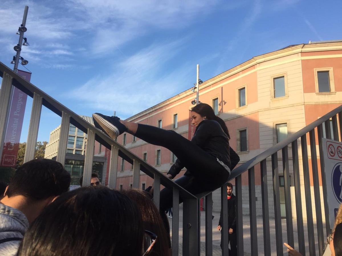 Una estudiante de la UPF, salta la valla para ir a clase, esquivando el piquete de huelga.