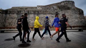 Un grupo de migrantes detenidos es conducido a un vehículo policial en el centro de Ceuta. Al fondo de la imagen, las murallas de la ciudad.