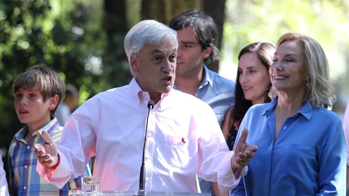 Piñera, junto a su nieto y su mujer, Cecilia Morel, se dirige a la prensa tras votar en un colegio público, en Santiago, el 17 de diciembre.