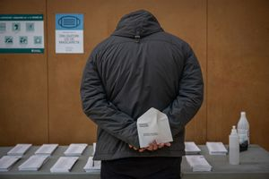 Un hombre consulta las papeletas de las elecciones catalanas en un colegio electoral