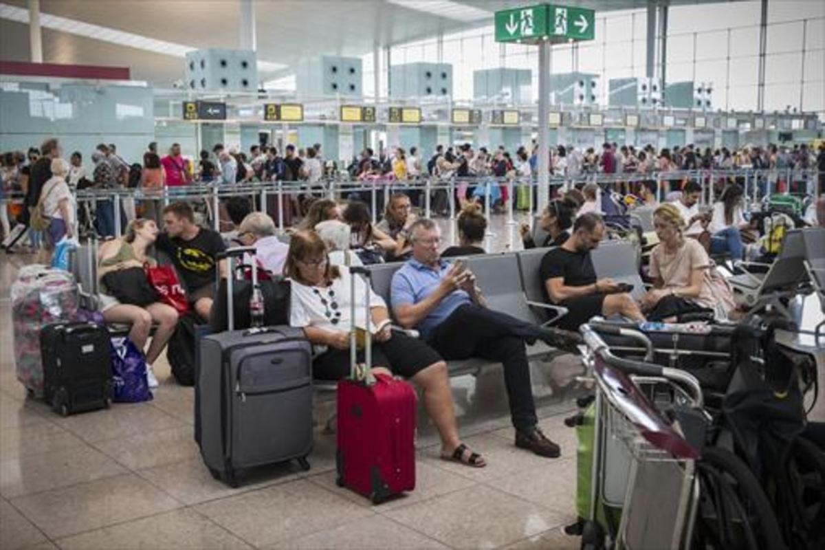 Colas frente al control de seguridad y pasajeros esperando en las instalaciones del aeropuerto de El Prat.