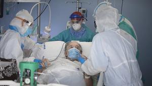 Varios sanitarios atienden a un enfermo con coronavirus en la uci de un hospital.