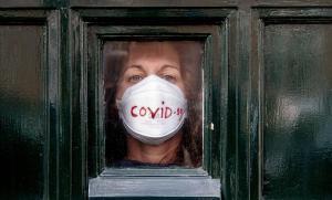 Una mujer mira al exterior desde la puerta de su casa,en La Haya, donde permanece en cuarentena por el coronavirus.