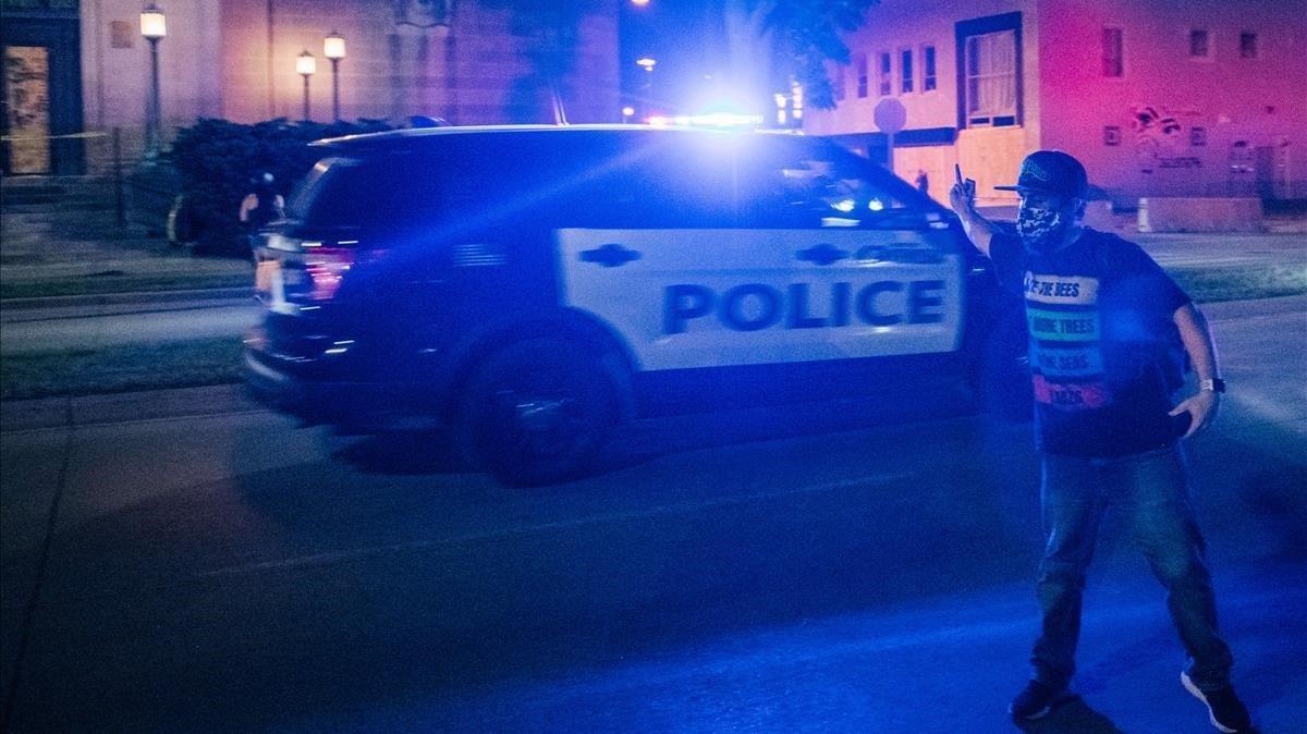 Un manifestante gesticula ante el paso de un vehículo de policía, la noche del miércoles en Kenosha.