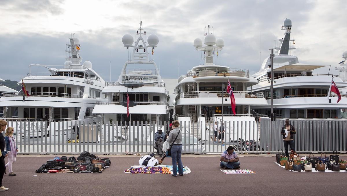 Barcos de lujo y manteros en el Port Vell de Barcelona.