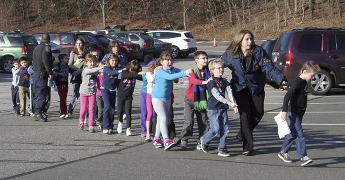 Una profesora acompaña a sus alumnos fuera de la escuela donde se ha producido el tiroteo.