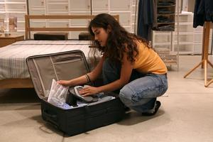 Una joven prepara su equipaje de mano para un viaje en avión.