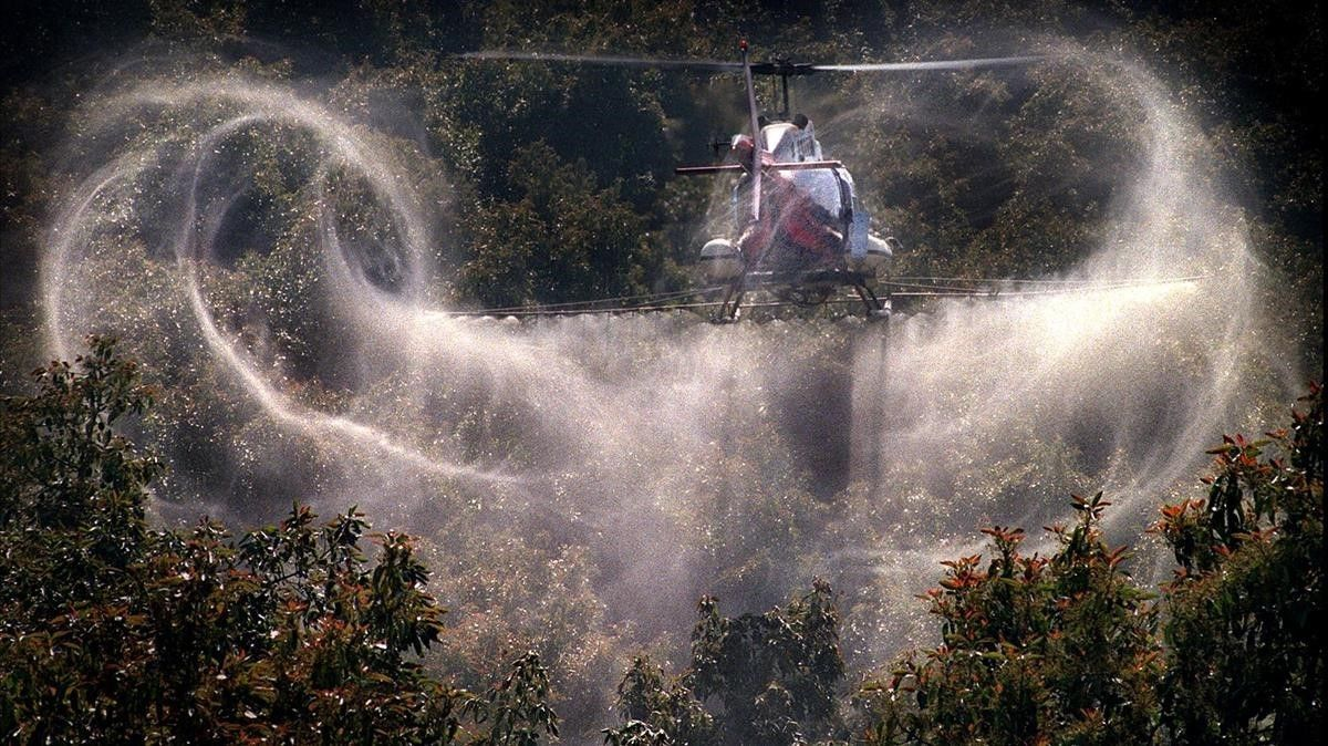 Un aspersor riega con pesticidas un campo de cultivo.