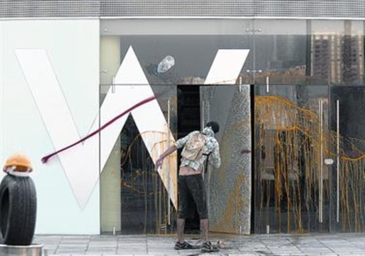 Un manifestante lanza pintura contra una de las fachadas del hotel, al finalizar la protesta lúdica, ayer.