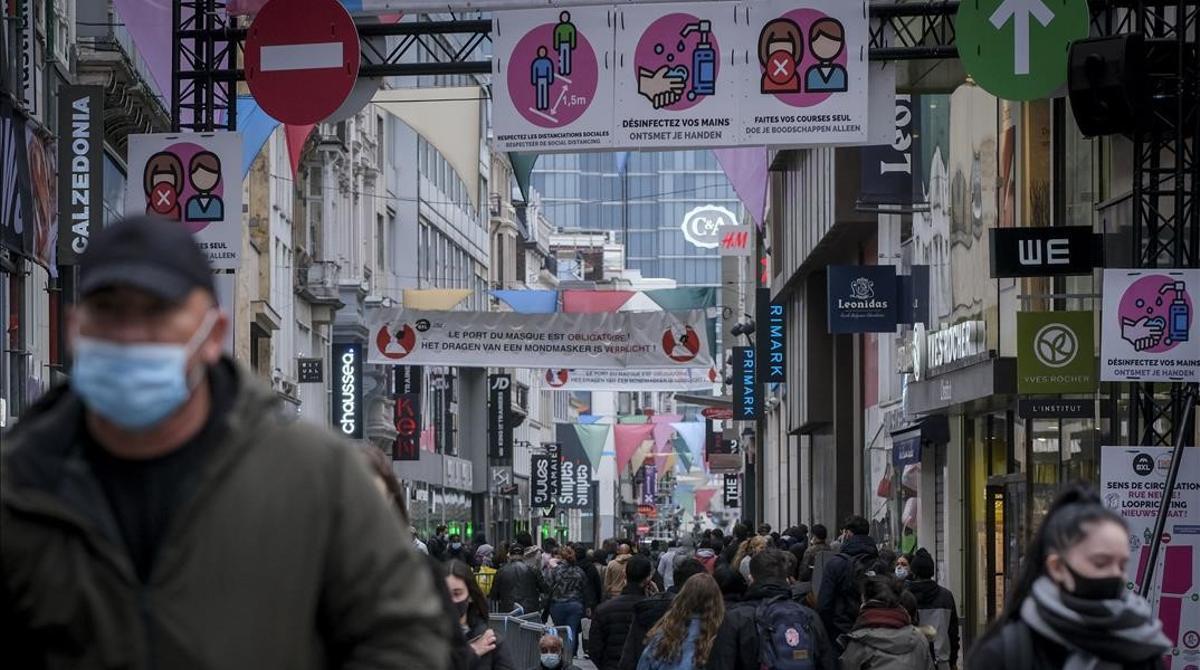 Paseantes con mascarilla por una de las principales calles de compras en Bruselas.
