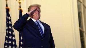 Trump saluda a la bandera desde el balcón deTruman dela Casa Blanca.