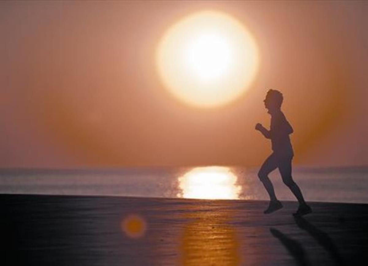 Un corredor trota por el frente marítimo de Barcelona, esta semana,  al amanecer.