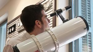Un aficionado mira a través de un telescopio.