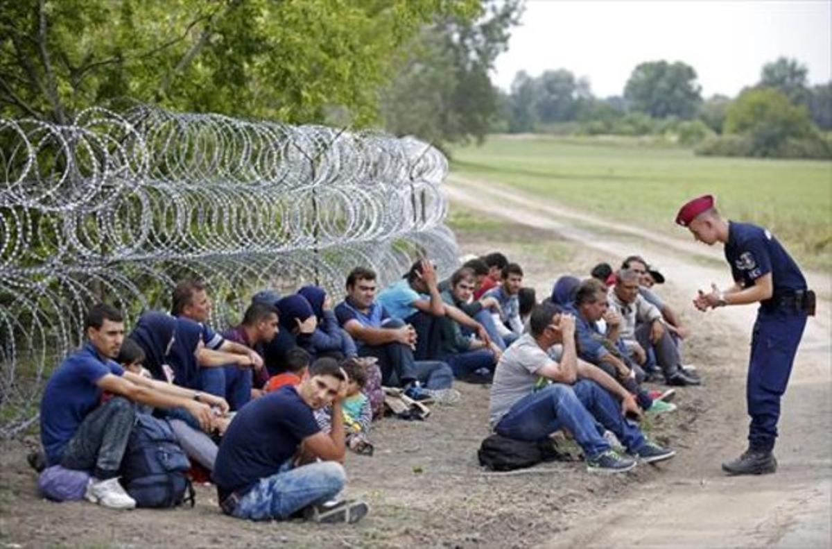 Un policía húngaro con varios detenidos tras cruzar desde Serbia.