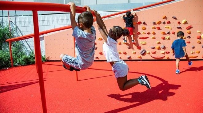 Niños jugando en el nuevo rocódromo frente a laEscola La Pau.