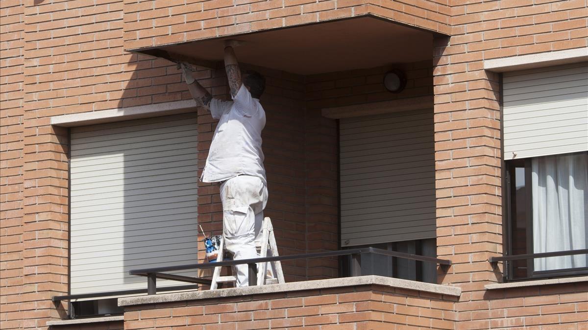 Un pintor realiza un trabajo en una terraza de un cuarto piso sin medidas de protección.