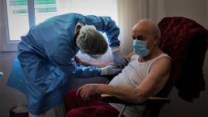 Un sanitario de la Unidad de Hospitalitació a Domicilio de Can Ruti atendiendo a un paciente con covid-19.