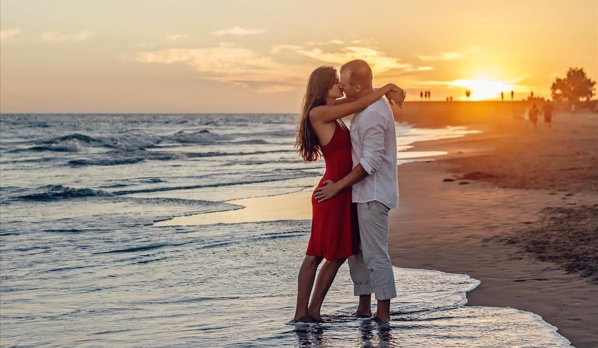 Una pareja besándose en la playa, la típica estampa del amor veraniego.