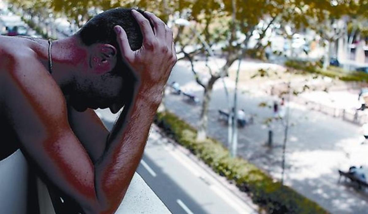 Un joven, en un balcón ante una calle de Barcelona.