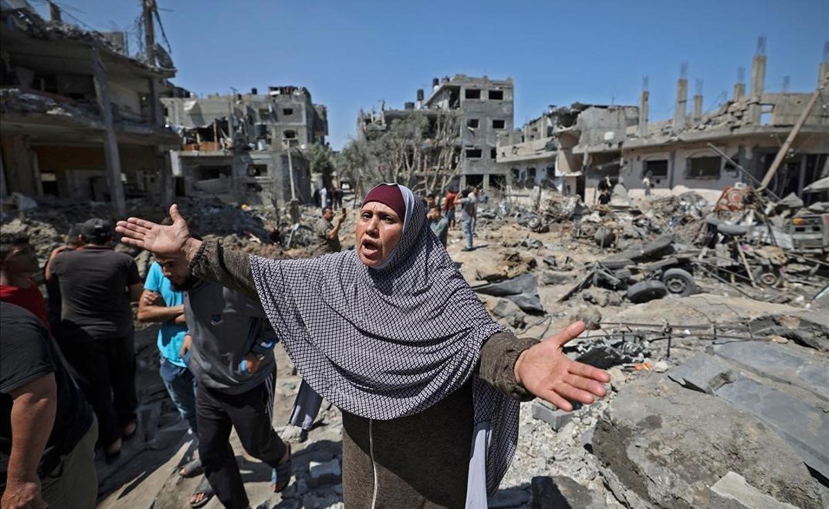 Una mujer palestina gesticula mientras un grupo de gente observa los daños causados por un ataque aéreo israelí en Beit Hanun, en el norte de la Franja de Gaza.