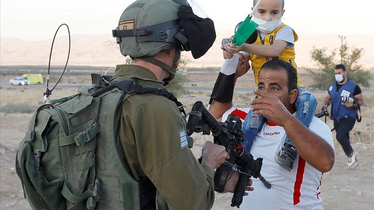 Un soldado israelí apunta con su arma al pecho de un palestino con su hijo en una protesta el martes contra el plan de anexión de Cisjordania.