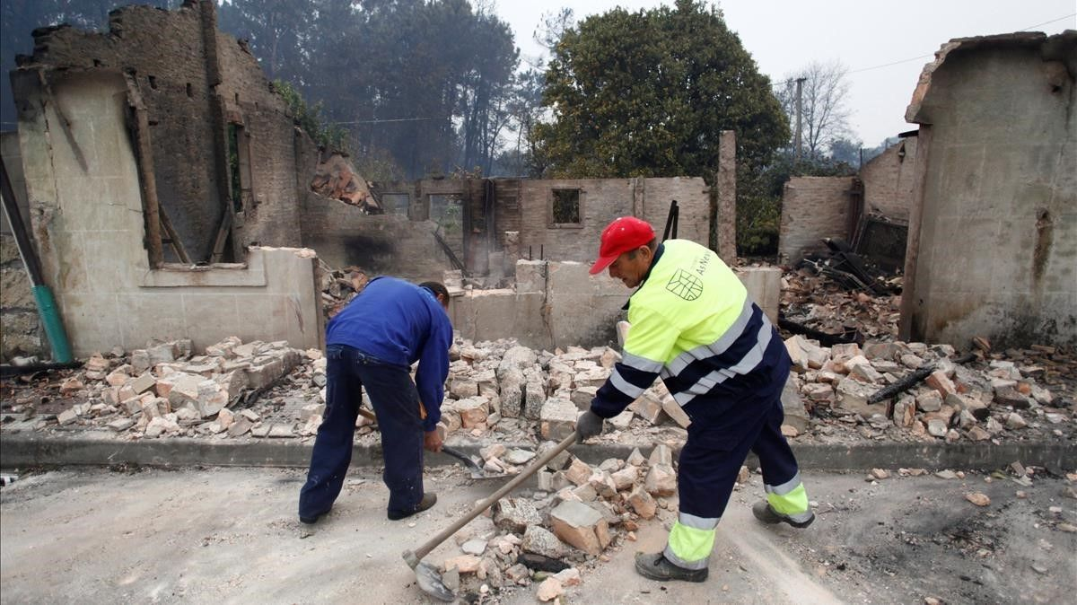 Dos operarios del concello pontevedrés de As Nevesretiraban los cascotes de una casa derribada tras ser pasto del fuego.