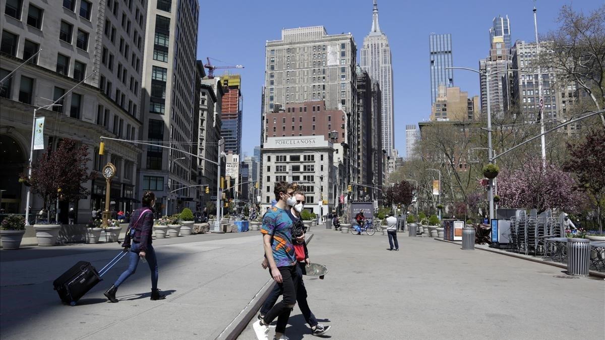 Unos turistas caminan frente alEmpire Stateen el barriodeMadisonSquare de Nueva York.