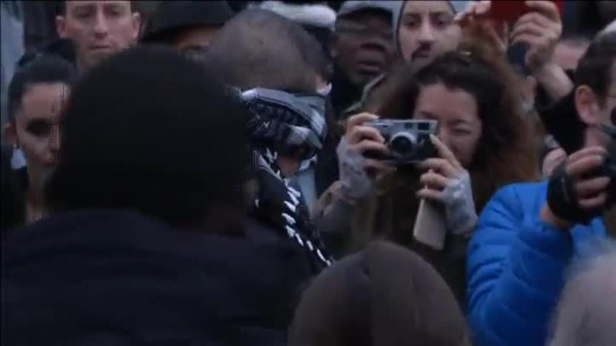 Un joven musulmán, con un pañuelo atado en la cabeza, pide confianza y abrazos en plena Plaza de la República de París.