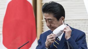 Shinzo Abe, primer ministro japonés, se quita la mascarilla.
