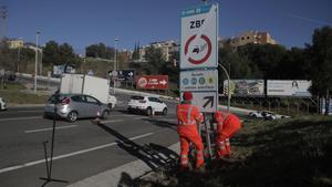 Unos operarios colocan una de las señales que restringe la circulación a los vehículos más contaminantes en L'Hospitalet de Llobregat, esta mañana