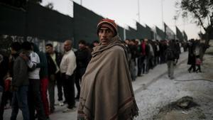 Un refugiado, cubierto con una manta, junto a la cola de distribución de comida en el campo de Moria, en Lesbos, en una imagen de archivo.