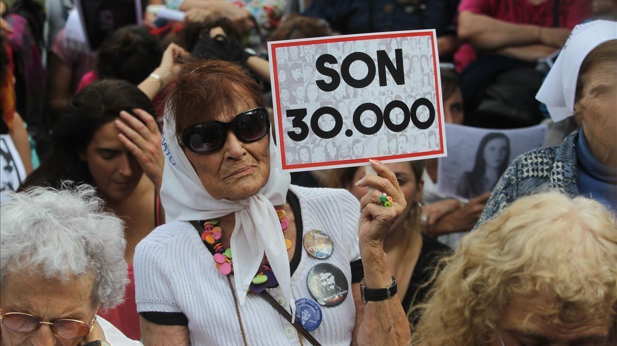Una mujer sostiene un cartel en referencia a los 30.000 desaparecidos mientras escucha el veredicto por los crímenes cometidos en la ESMA, en Buenos Aires, el 29 de noviembre.