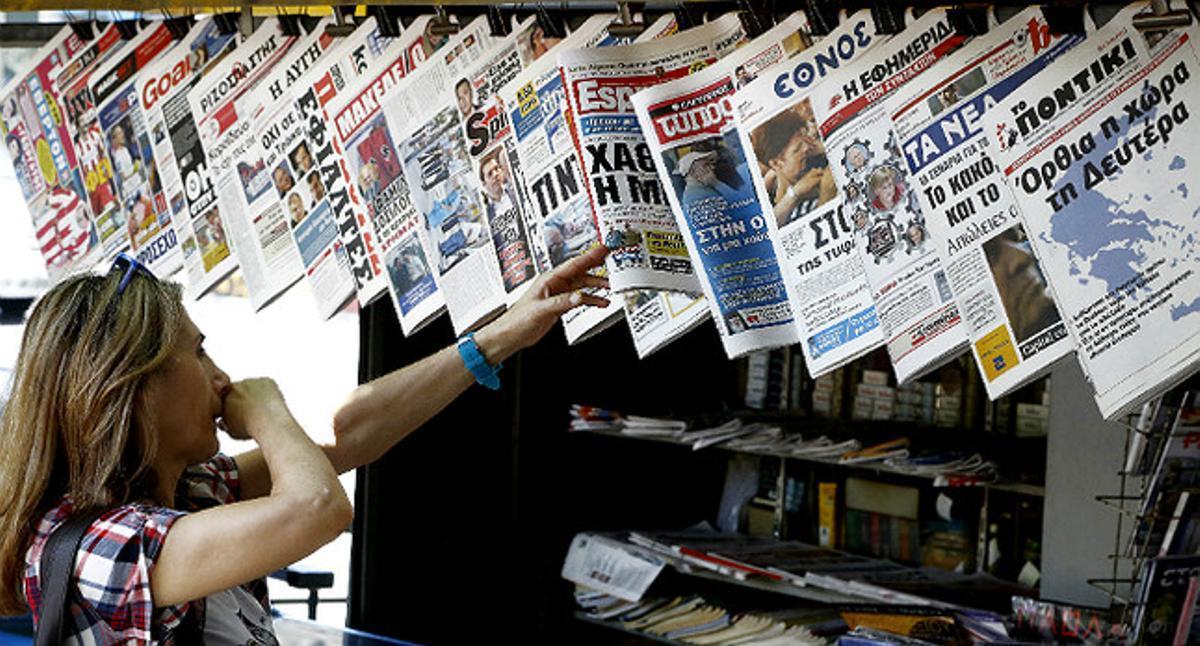Una mujer mira con curiosidad y cierto temor la oferta informativa de la prensa griega.