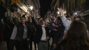 Turistas franceses cantan animados a las puertas de un bar de Madrid.