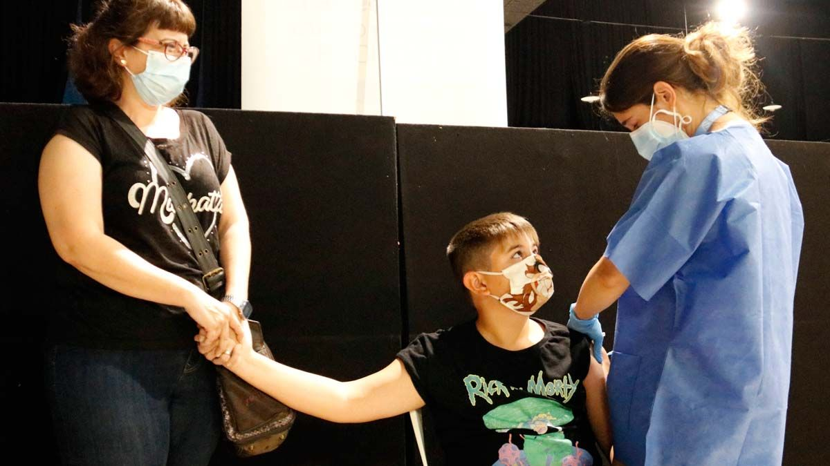 Jóvenes de 12 a 15 años se vacunan en Tàrrega. En la foto, un chico acompañado de su madre.