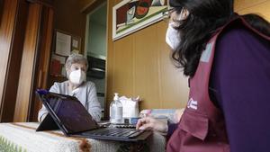 Lidia Abòs Olivares atiende a una empleada de la Diputación de Barcelona, después de que el organismo instalara en su casa un detector de humos.