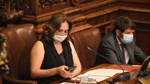 La alcaldesa de Barcelona, Ada Colau, observa su móvil en un pleno municipal.