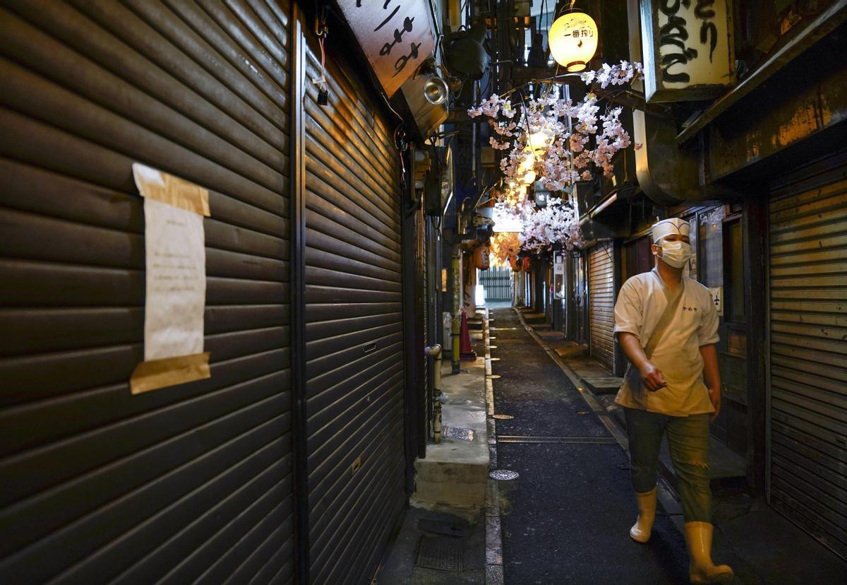 Un trabajador de un restaurante pasea por una zona de hostelería cerrada en Tokio