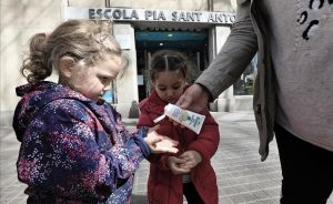 Dos niñas se aplican gel desinfectante al salir de la escuela, el pasado 12 de marzo en Barcelona.