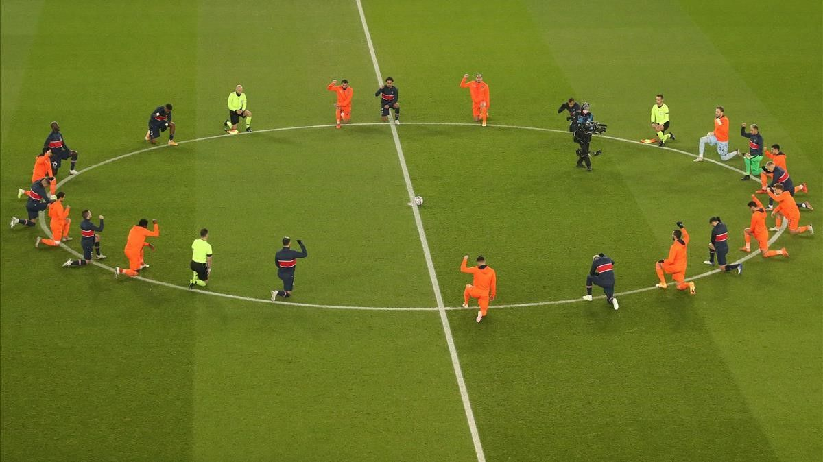 TOPSHOT - Football players and referees kneel on the pitch against racism before the UEFA Champions League group H football match between Paris Saint-Germain (PSG) and Istanbul Basaksehir FK at the Parc des Princes stadium in Paris  on December 9  2020  (Photo by XAVIER LAINE   POOL   AFP)