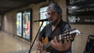 El cantautor Marcelo Castro toca una canción sobre el coronavirus en la estación de Maria Cristina del metro de Barcelona.