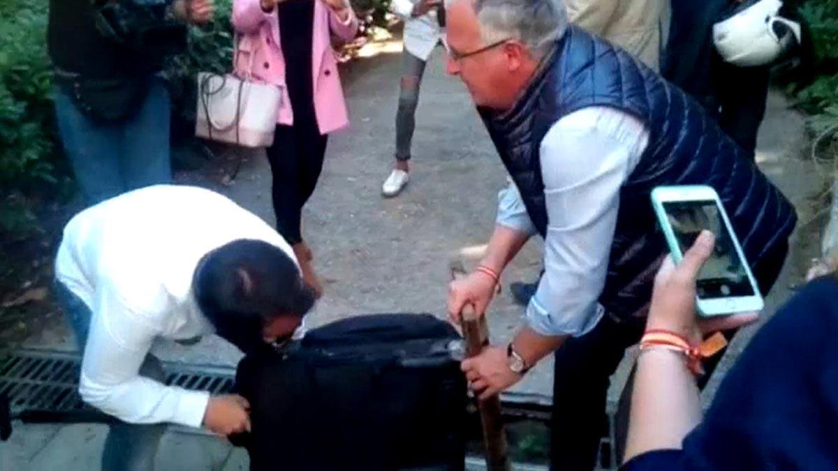 Josep Bou (PP) ayuda a una periodista a desencallar una maleta con ruedas de un desagüe.