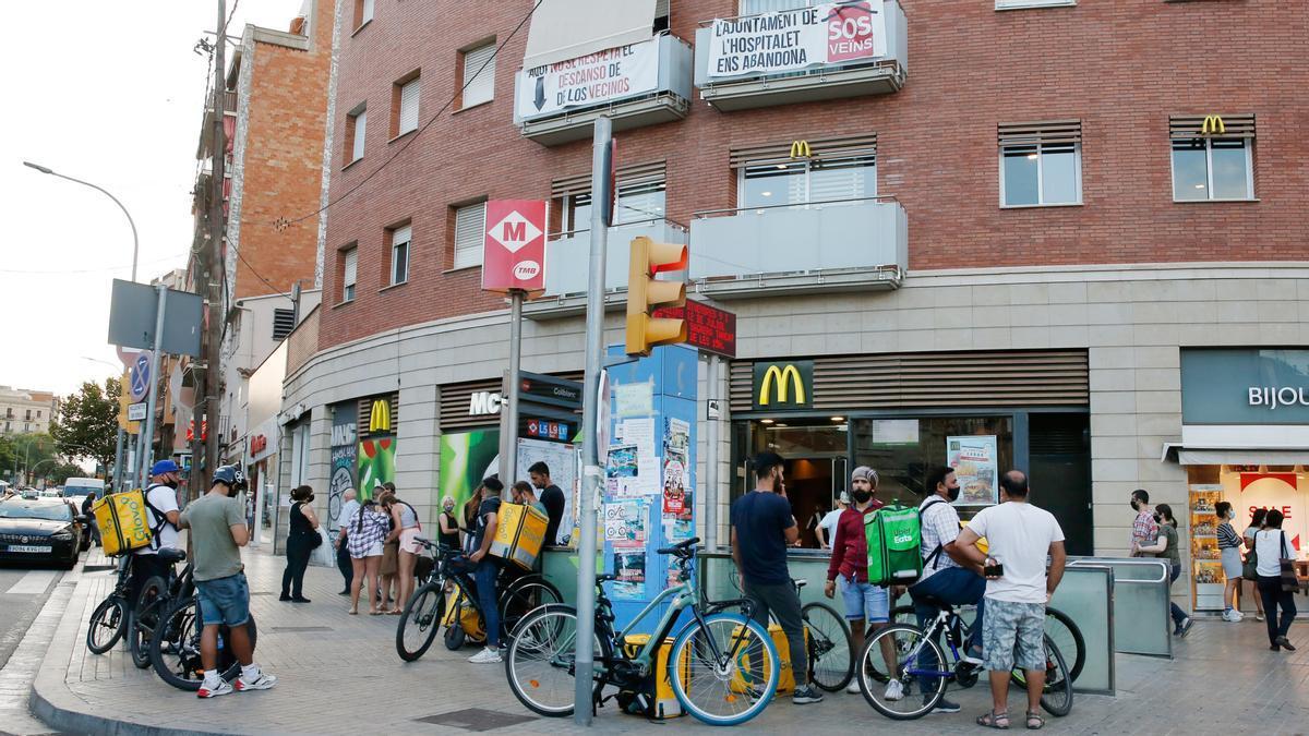 Varios 'riders' esperan pedidos a la entrada de un McDonald´s en Collblanc, l'Hospitalet del Llobregat.